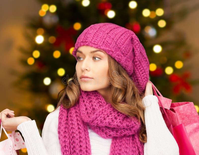 Kvinna med shoppingpåsar över julljus royaltyfri fotografi