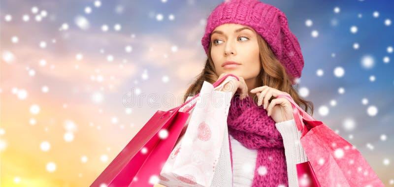 Kvinna med shoppingpåsar över snöbakgrund arkivbild
