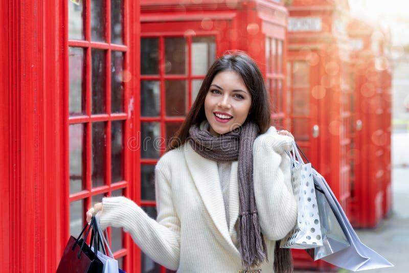 Kvinna med shoppingpåsar framme av röda telefonbås i London, UK royaltyfri fotografi