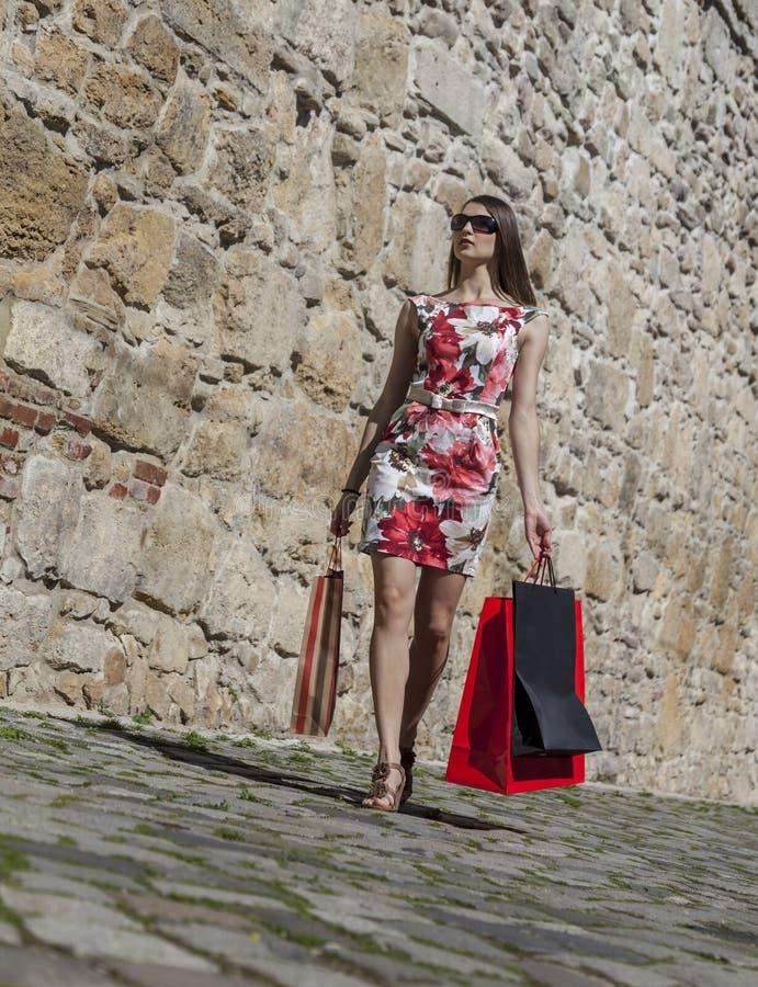 Kvinna med shoppingpåsar i en stad arkivfoton