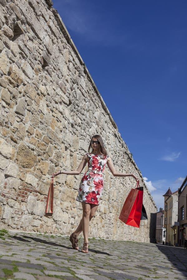 Kvinna med shoppingpåsar i en stad royaltyfri fotografi