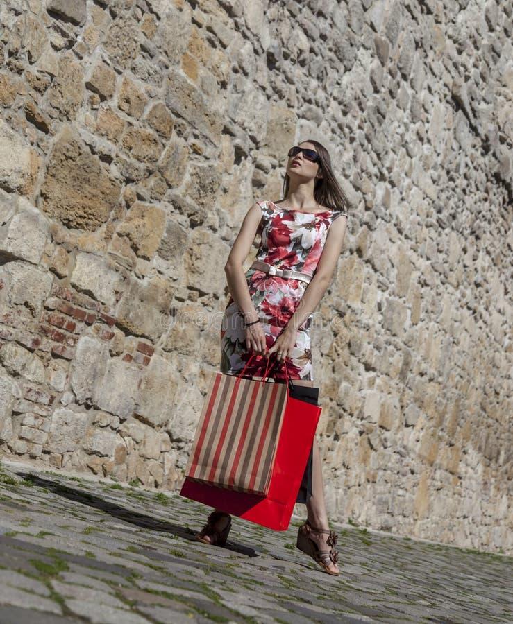 Kvinna med shoppingpåsar i en stad arkivfoto