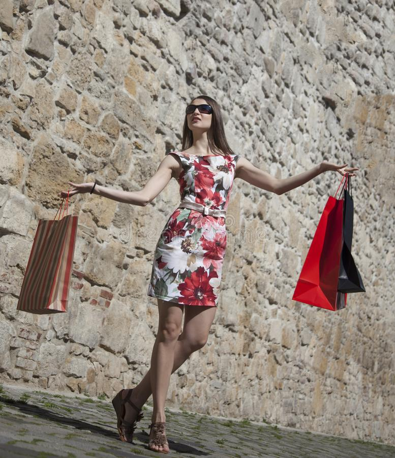 Kvinna med shoppingpåsar i en stad arkivbilder