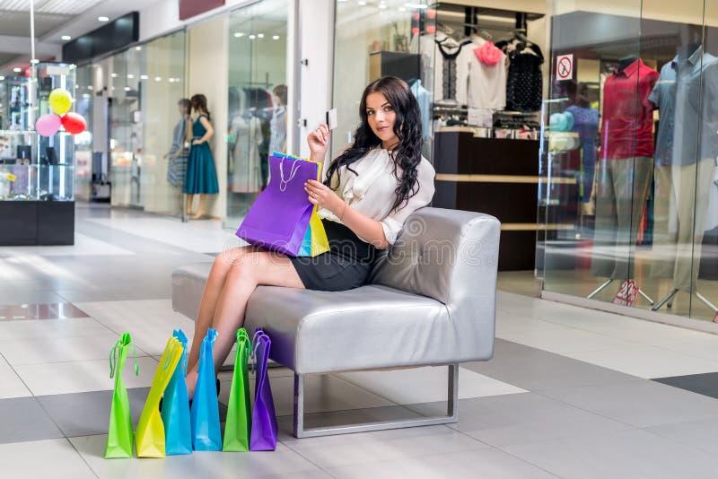 Kvinna med shoppingpåsar och kreditkort som sitter på soffan royaltyfri bild