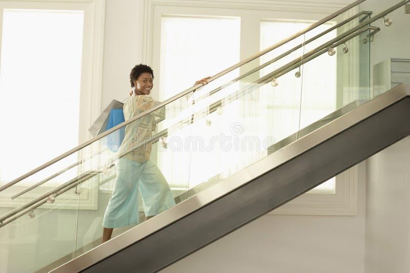 Kvinna med shoppingpåsar på modern Glass trappa arkivfoton