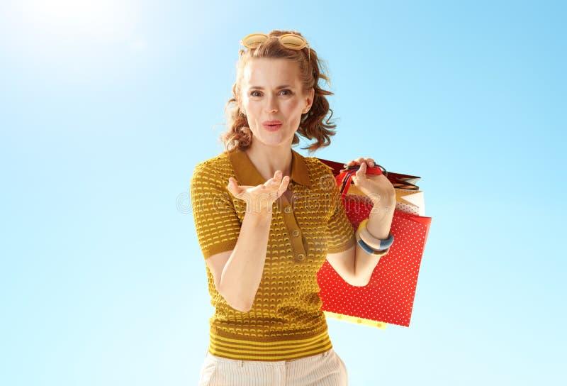 Kvinna med shoppingp?sar som bl?ser luftkyssen mot bl? himmel arkivfoto