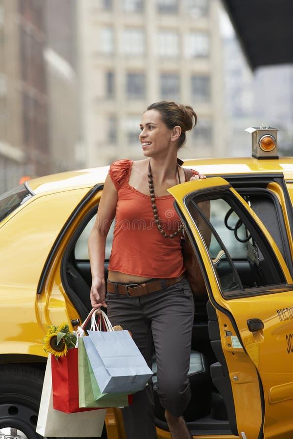 Kvinna med shoppingpåsar som går ut taxien arkivfoton