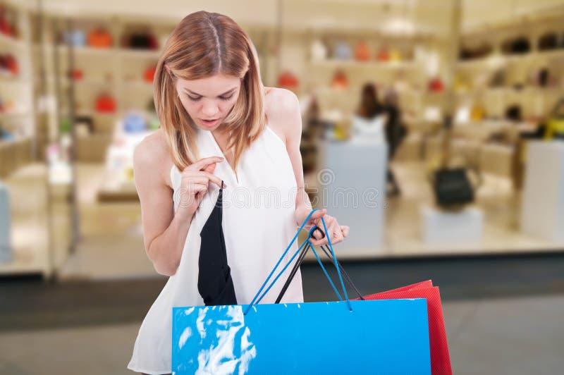 Kvinna med shoppingpåsar som kopplar av på gallerian arkivbild