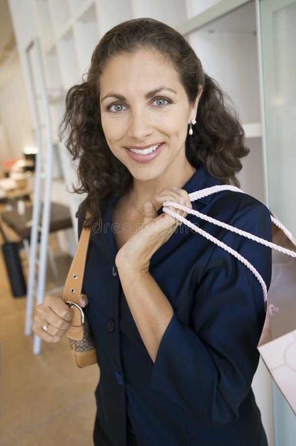 Kvinna med shoppingpåsar som står i stående för möblemanglager royaltyfri fotografi