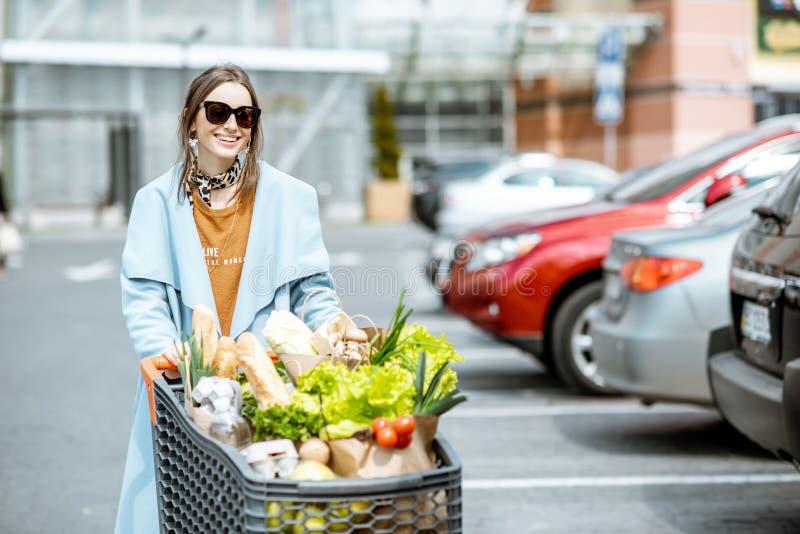Kvinna med shoppingvagnen mycket av matoutdooors royaltyfri fotografi