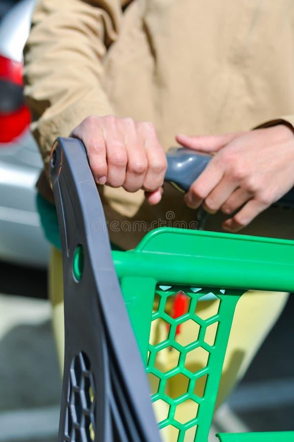 Kvinna med shoppingvagnen på bilparkering arkivfoton