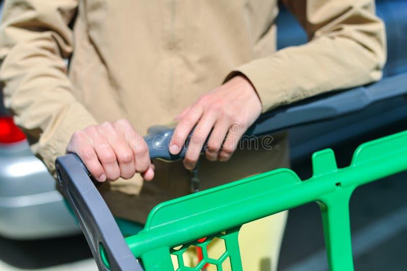 Kvinna med shoppingvagnen på bilparkering arkivbild