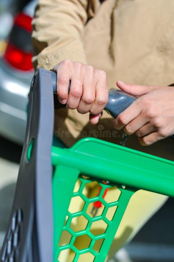 Kvinna med shoppingvagnen på bilparkering fotografering för bildbyråer