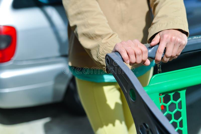 Kvinna med shoppingvagnen på bilparkering royaltyfri foto