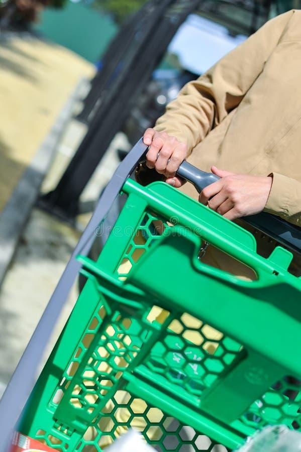 Kvinna med shoppingvagnen på bilparkering arkivbilder