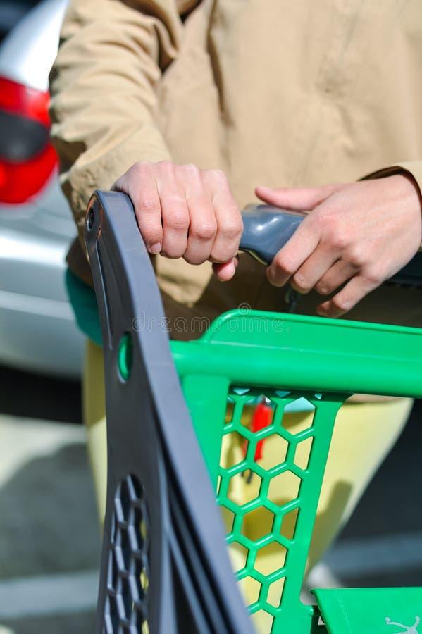 Kvinna med shoppingvagnen på bilparkering royaltyfri fotografi