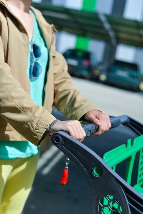 Kvinna med shoppingvagnen på bilparkering arkivfoto