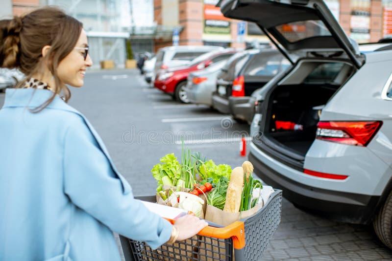 Kvinna med shoppingvagnen på den utomhus- parkeringen fotografering för bildbyråer