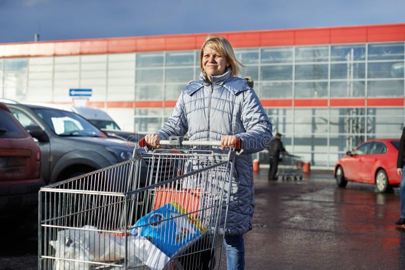 Kvinna med shoppingvagnen på parkering royaltyfria bilder
