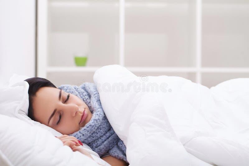 Kvinna med sjuka förkylningar för termometer, influensa, feber, huvudvärk i säng arkivfoton