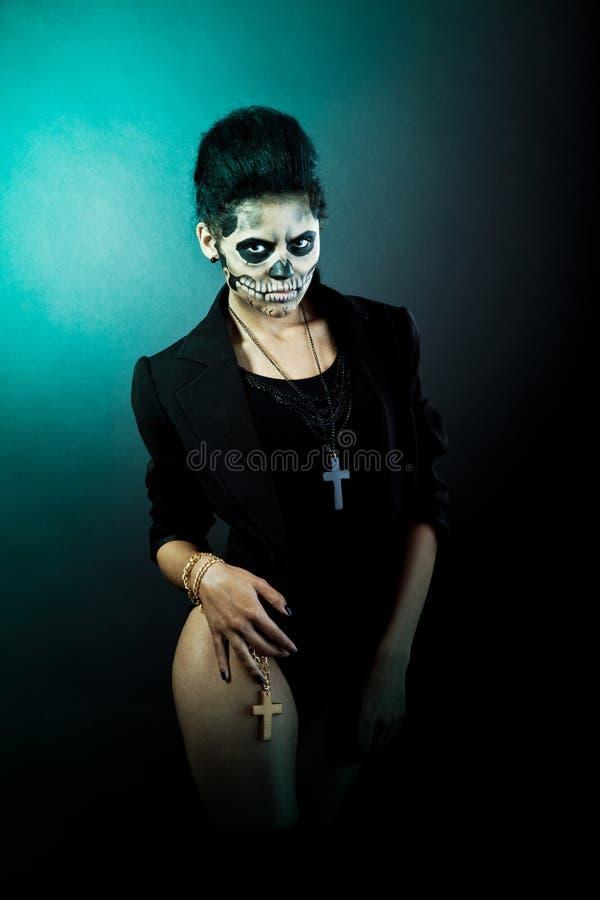 Kvinna med skalleframsidan. Halloween framsidakonst royaltyfri bild