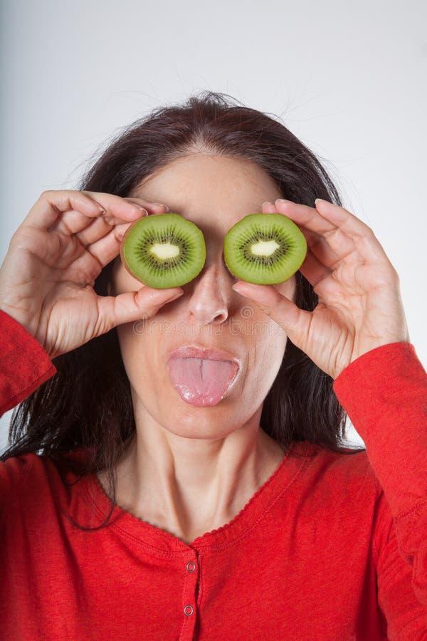 Kvinna med skivade kiwier på ögon och att klibba ut tungan arkivbilder