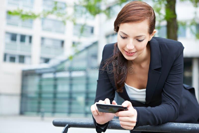 Kvinna med smartphone i internet arkivfoto