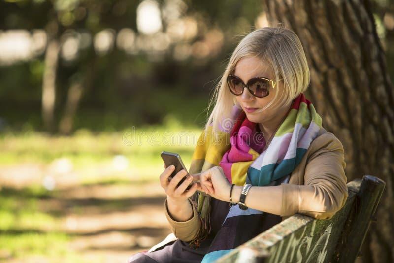 Kvinna med smartphonen i händer som sitter på bänk i parkera royaltyfria foton