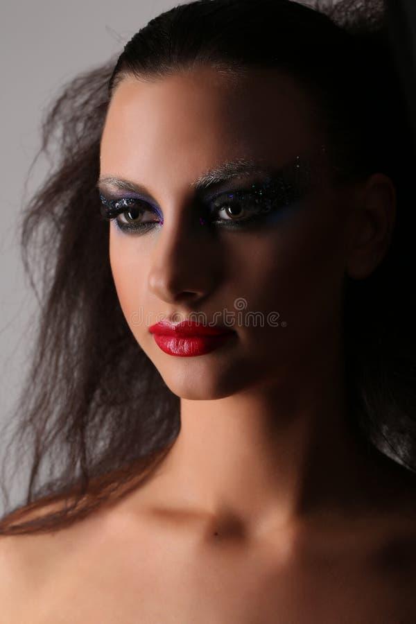 Kvinna med smokeyögon och löst hår close upp Grå färgbakgrund royaltyfri bild