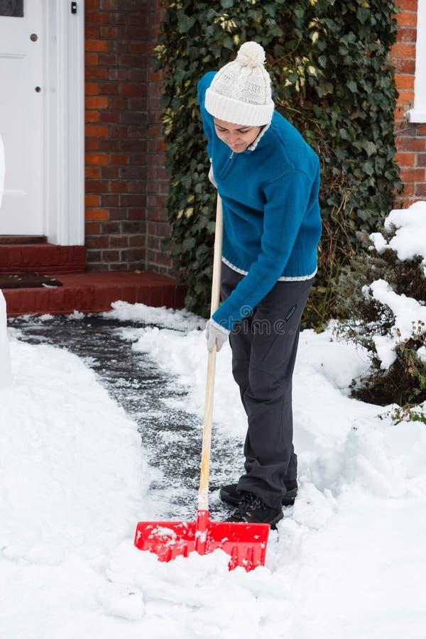 Kvinna med snowskyffeln arkivfoto