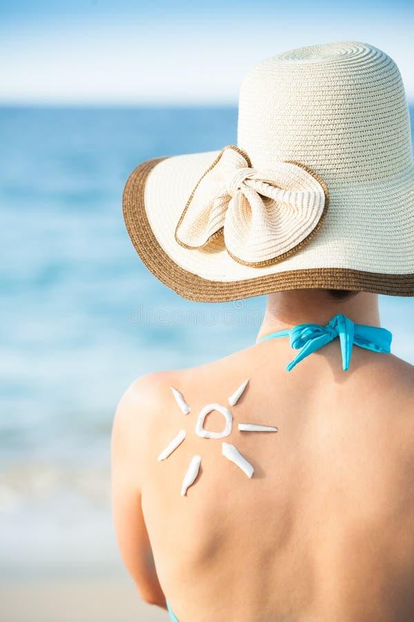 Kvinna med solen som dras från sunscreen på baksida royaltyfria foton