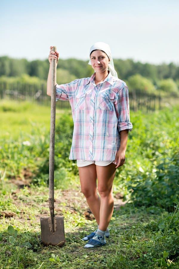 Kvinna med spaden i trädgård royaltyfri foto