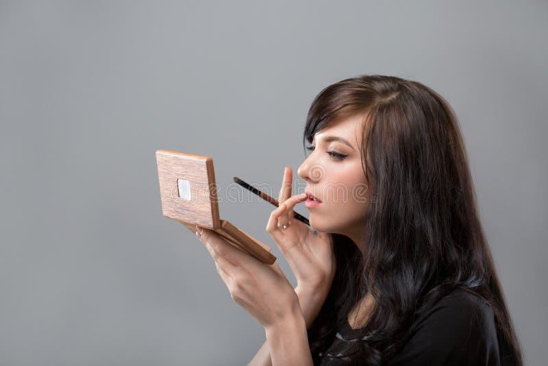 Kvinna med spegeln Härlig ung kvinna som har smink och ser i spegeln härlig för studiokvinna för par dans skjutit barn Grå färgba fotografering för bildbyråer