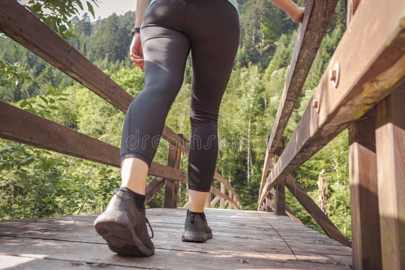 Kvinna med sportdräkten som går på en bro in i skogen arkivbild