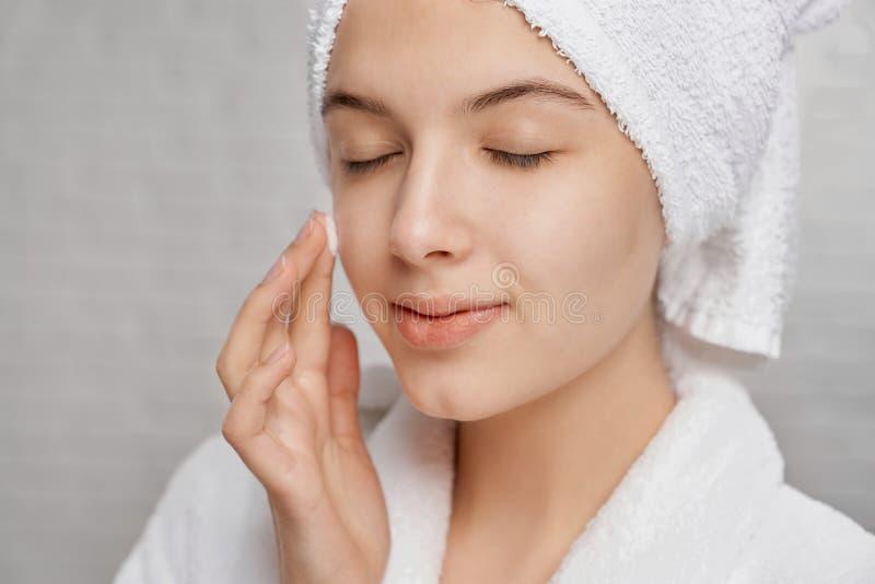 Kvinna med stängda ögon som applicerar fuktighetsbevarande hudkräm på framsida arkivfoto