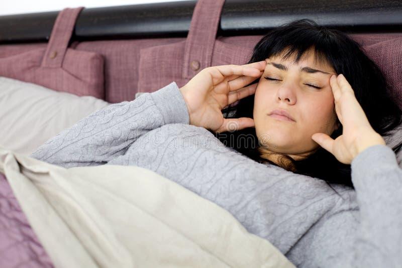 Kvinna med stark huvudvärk och feber som ligger i säng royaltyfri bild