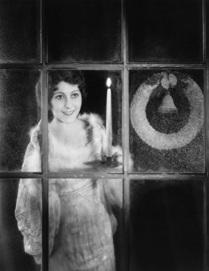 Kvinna med stearinljuset och julkransen i fönster (alla visade personer inte är längre uppehälle, och inget gods finns Leverantör royaltyfri bild