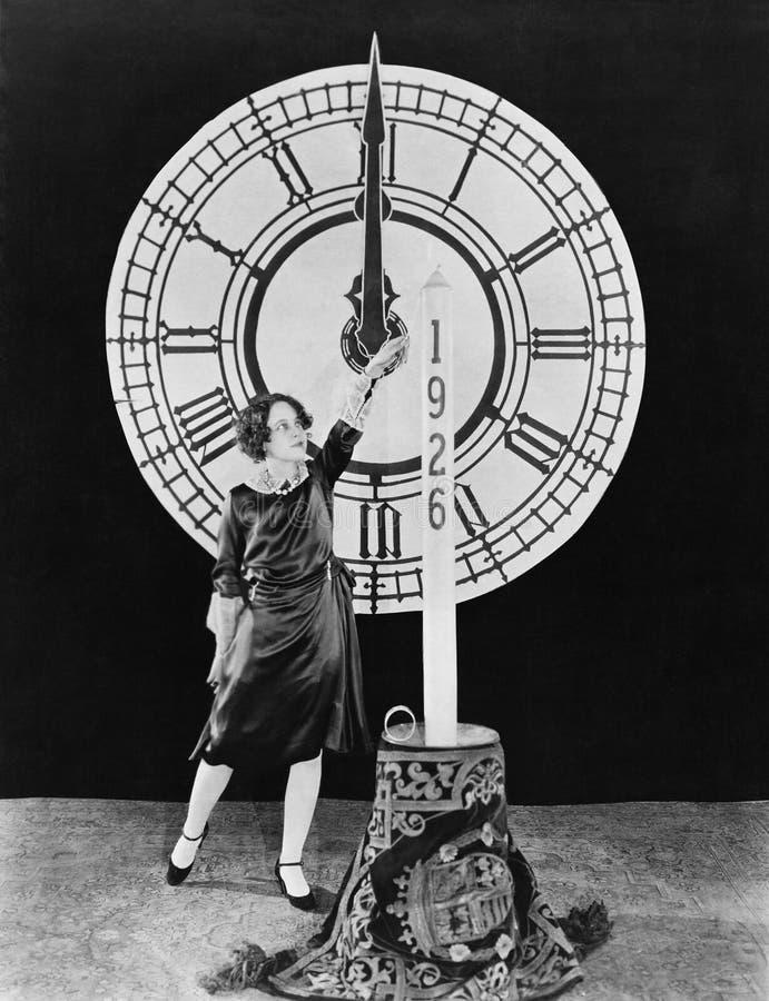 Kvinna med stearinljuset och klockan på helgdagsafton för nya år (alla visade personer inte är längre uppehälle, och inget gods f arkivfoton