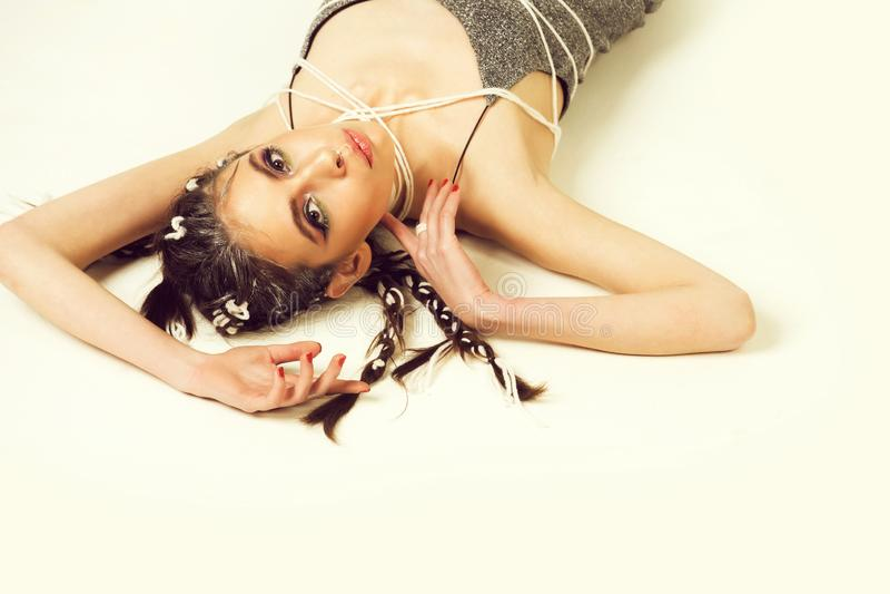 Kvinna med stilfulla flätade trådar och makeup som ligger på golv royaltyfria foton