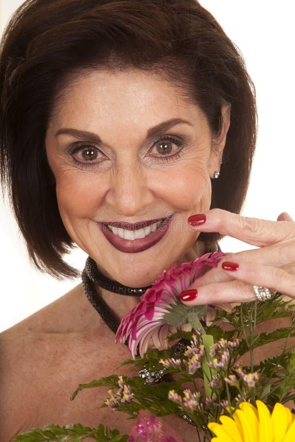 Kvinna med stort leende för blommaslut royaltyfria bilder