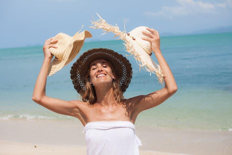 Kvinna med sugrörhattar på en härlig strand fotografering för bildbyråer