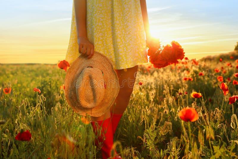 Kvinna med sugrörhatten och buketten av vallmo i solbelyst fält fotografering för bildbyråer