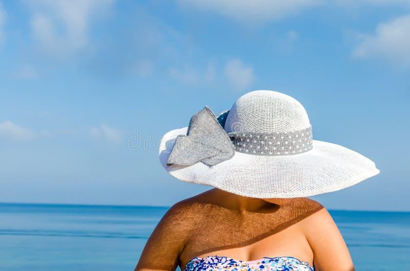 Kvinna med sugrörhatten som tycker om sommarferier royaltyfri foto