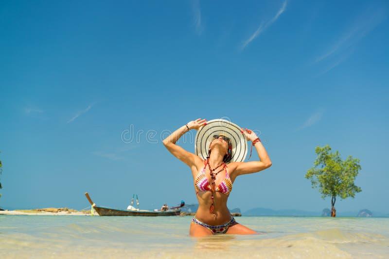 Kvinna med sugrörhatten som vilar på den tropiska stranden av Klong Muan royaltyfri fotografi