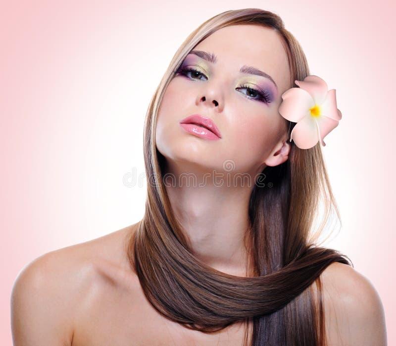 Kvinna med sunda långa hår och blommor fotografering för bildbyråer