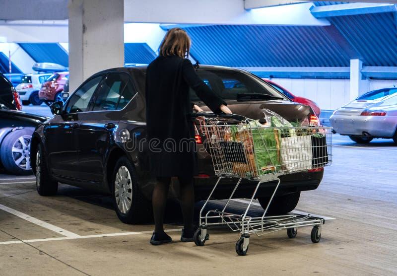 Kvinna med supermarketshoppingvagnen i parkering royaltyfri bild