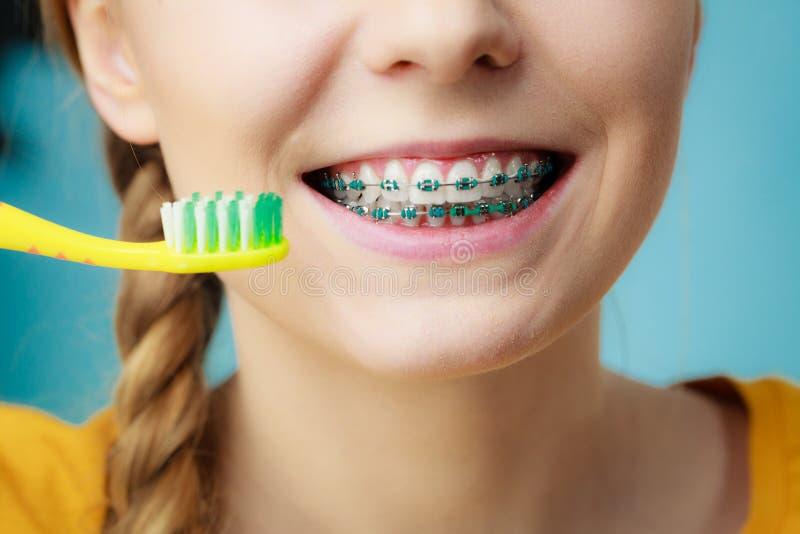 Kvinna med tandhänglsen genom att använda borsten royaltyfria foton