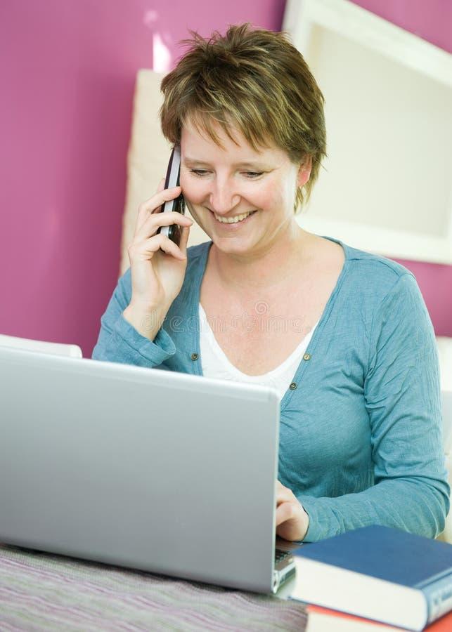 Kvinna med telefon- och anteckningsbokdatoren arkivbild