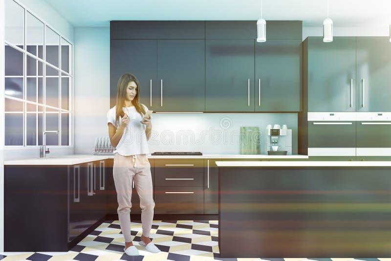 Kvinna med telefonen i vitt och grått kök royaltyfri foto