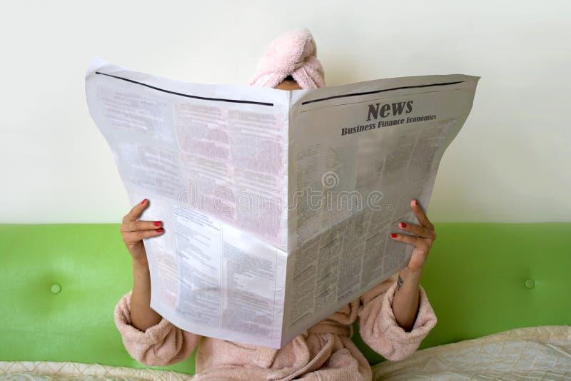 kvinna med tidningen Brunetten sitter på soffan hemma, når bad och den har läst arkivbild